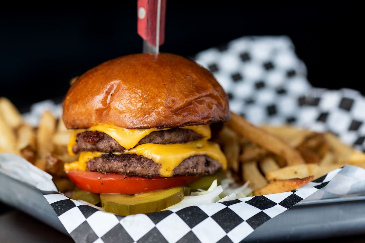 Burger and fries on a checkered parchment at The Greyhound in Glendale, California.