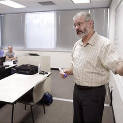 John Harvey teaches economics class at the University of Phoenix in Taylorsville. For-profit colleges face new regulations.