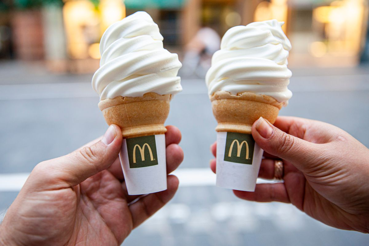 Two hands, each holding a McDonald's vanilla soft-serve cone.