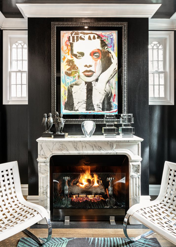 A living room area with a fireplace, two chairs, a framed painting on the wall, and original trefoil windows.