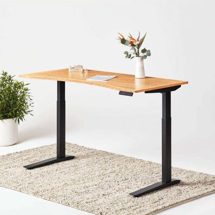 Wooden standing desk with black legs.