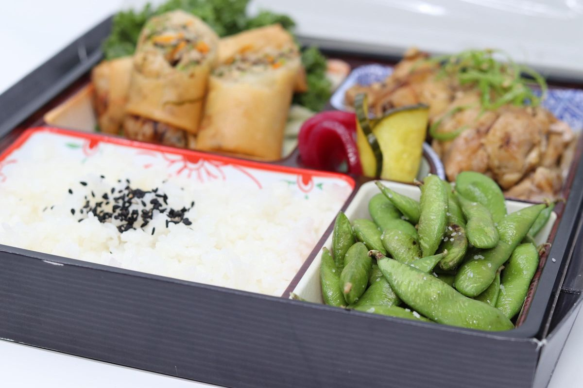 A bento box filled with edamame, steamed white rice, spring rolls, and teriyaki chicken
