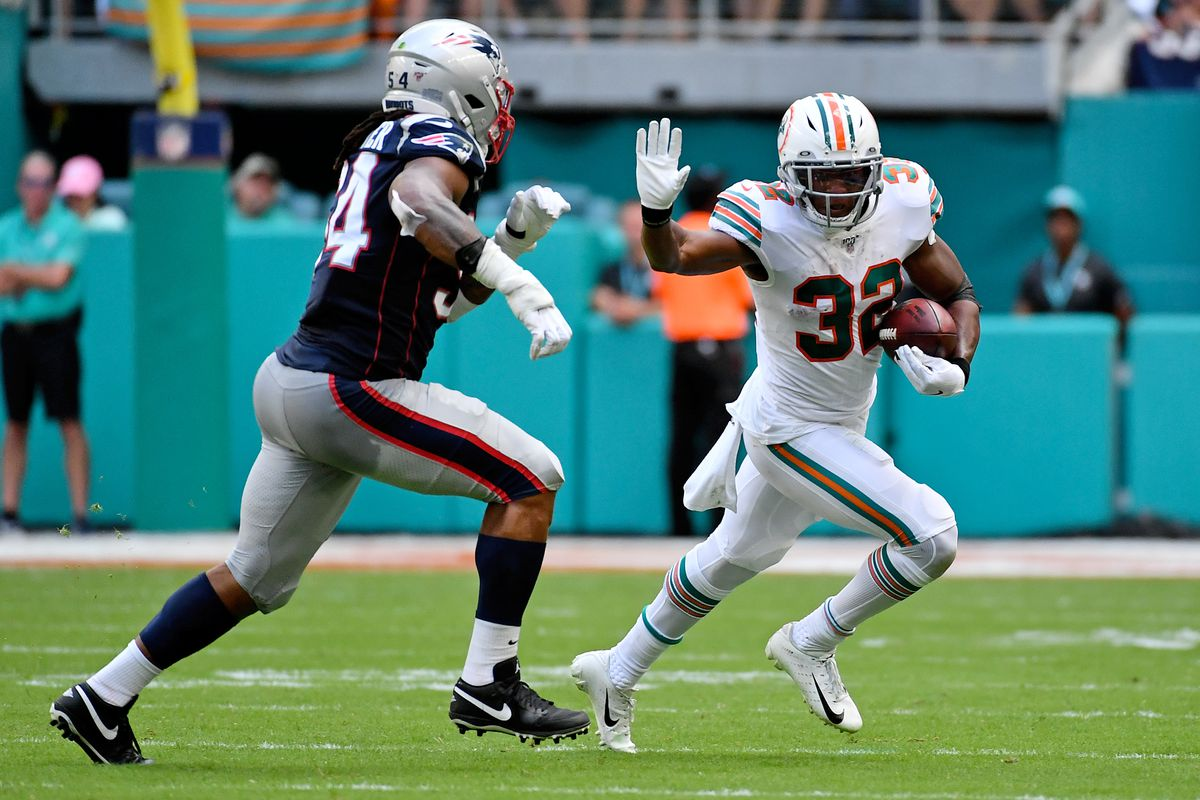 Miami Dolphins running back Kenyan Drake runs the ball around New England Patriots outside linebacker Dont'a Hightower during the first half at Hard Rock Stadium.