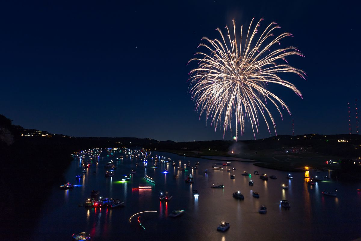 Big firework explosion over river with lighted boats