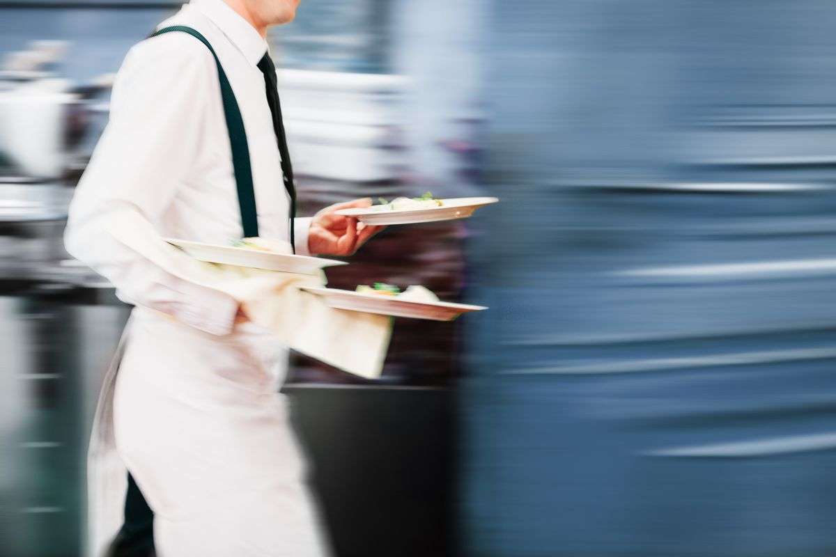 A waiter exits the kitchen in a blur of motion.