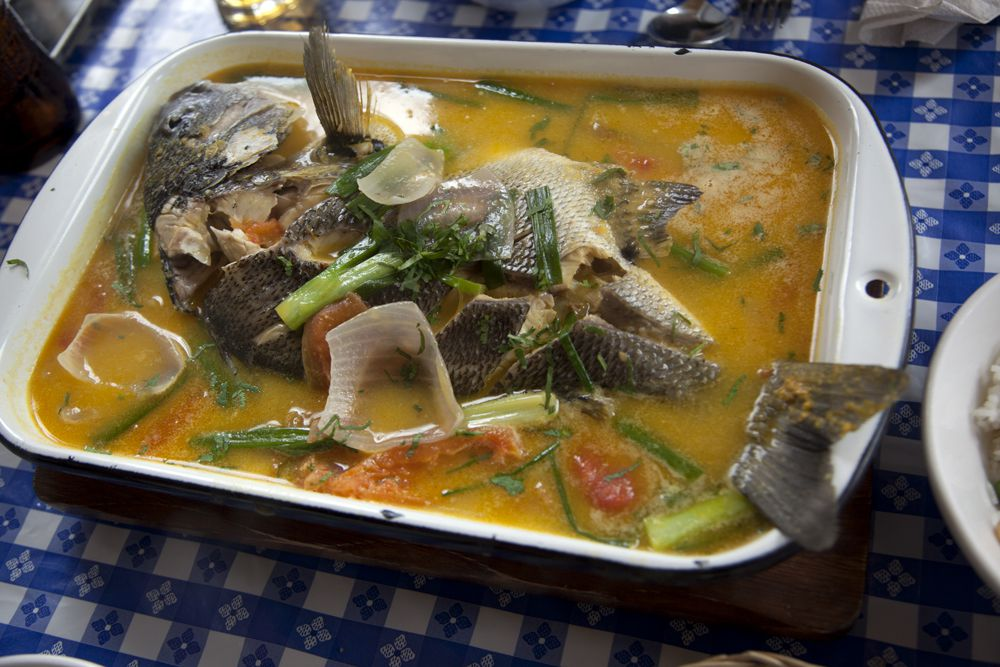 A full, skin-on fish is served in a large baking dish nearly filled with broth dotted with large chunks of vegetables.