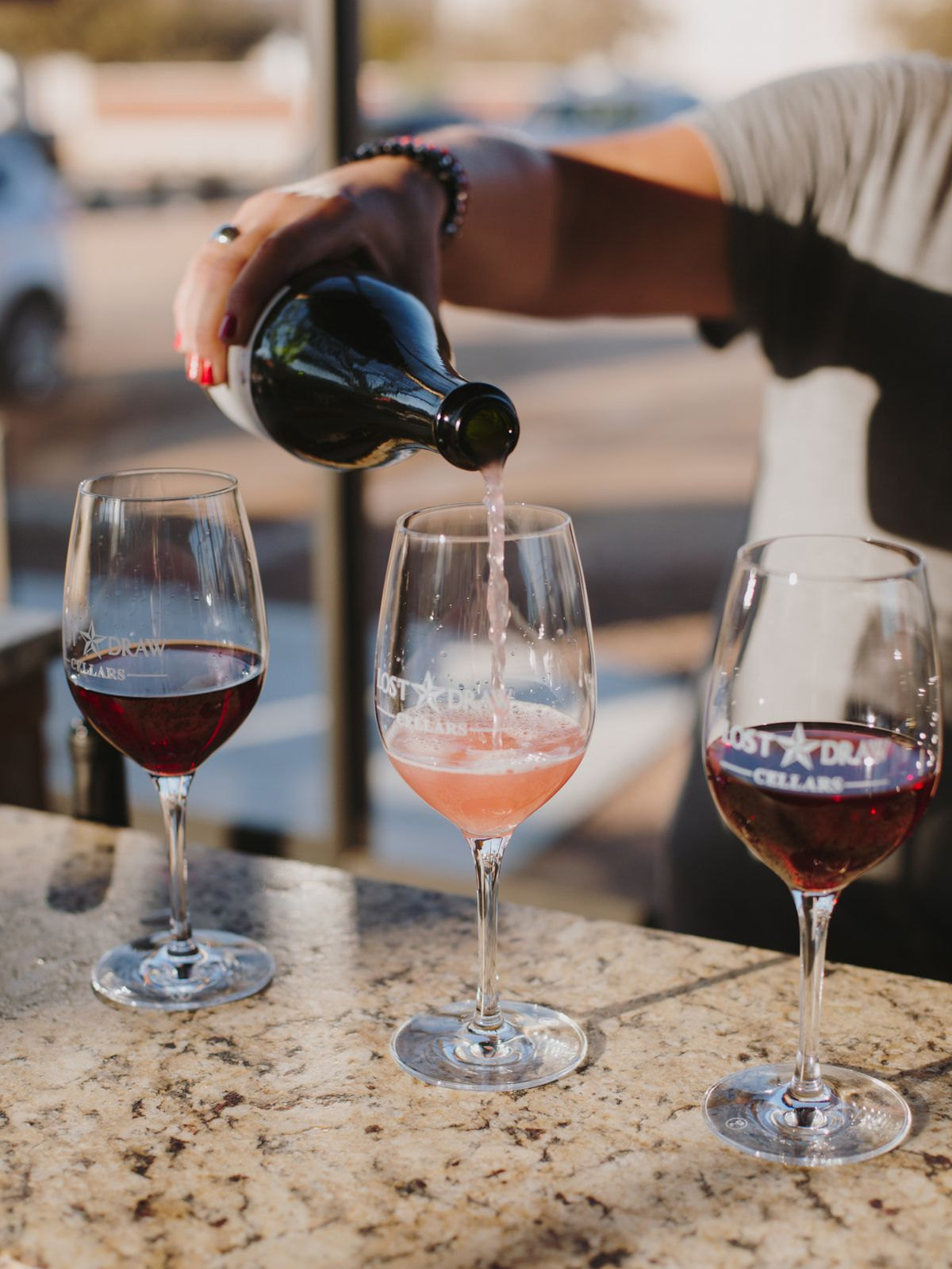 Pink wine is poured into an empty wine glass that is flanked on either side by a stem of red wine.