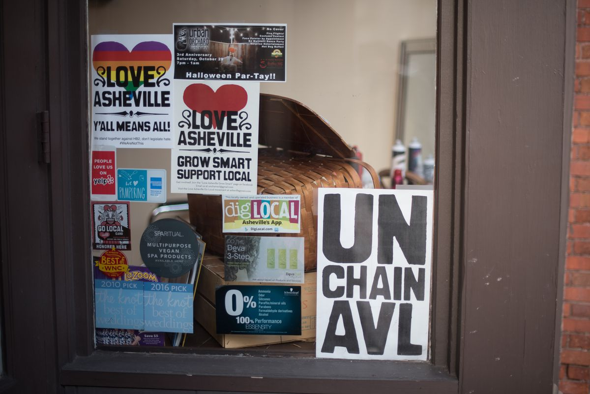 UnChain AVL signs promote independent small businesses. Glimpse into windows to catch music, moody lighting, and laughter.