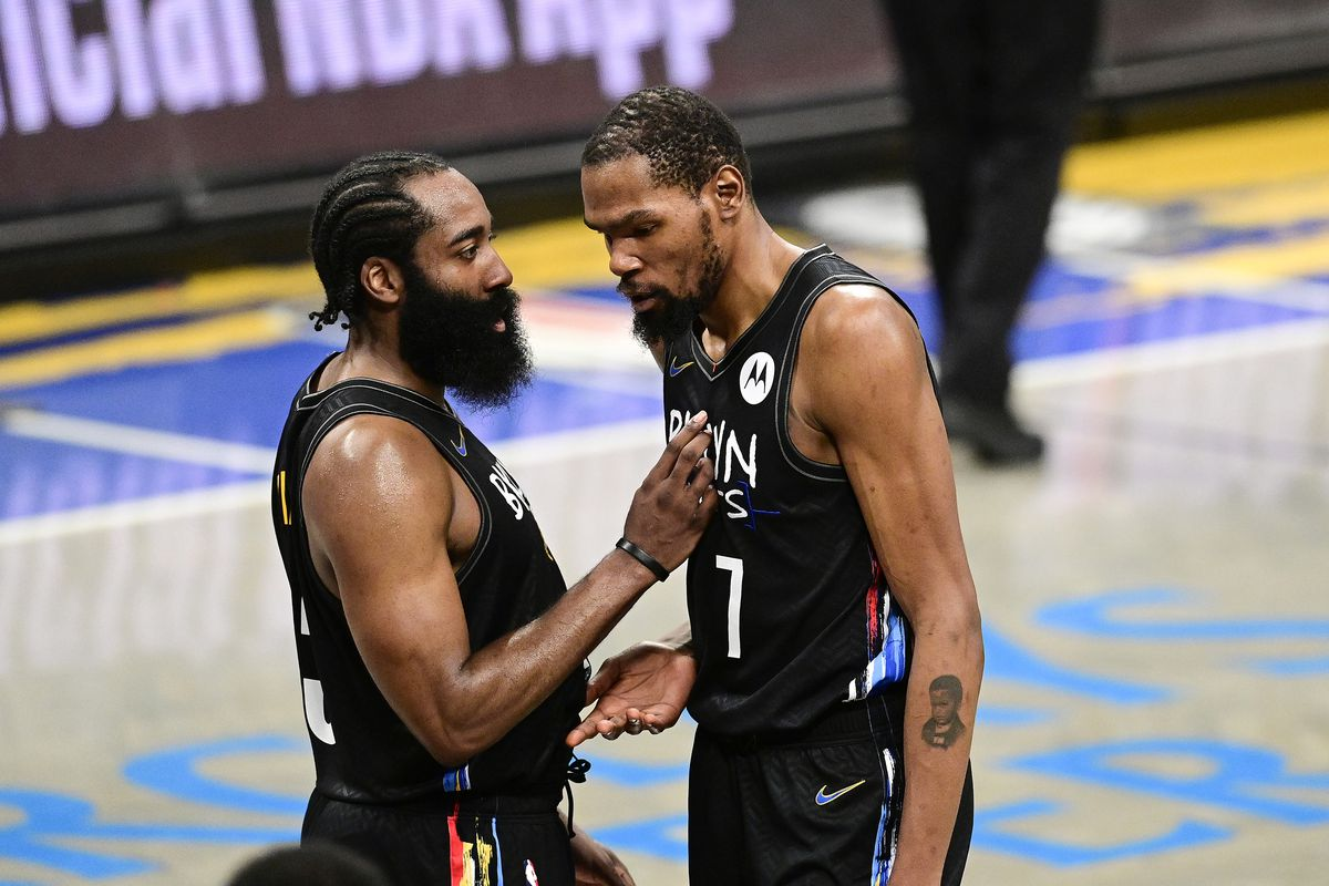 James Harden #13 and Kevin Durant #7 of the Brooklyn Nets speak during a timeout against the Boston Celtics in Game Five of the First Round of the 2021 NBA Playoffs at Barclays Center on June 01, 2021 in the Brooklyn borough of New York City.