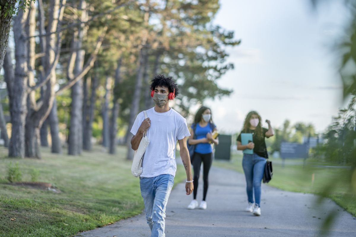 Group of students wearing reusable face masks while walking together on campus.