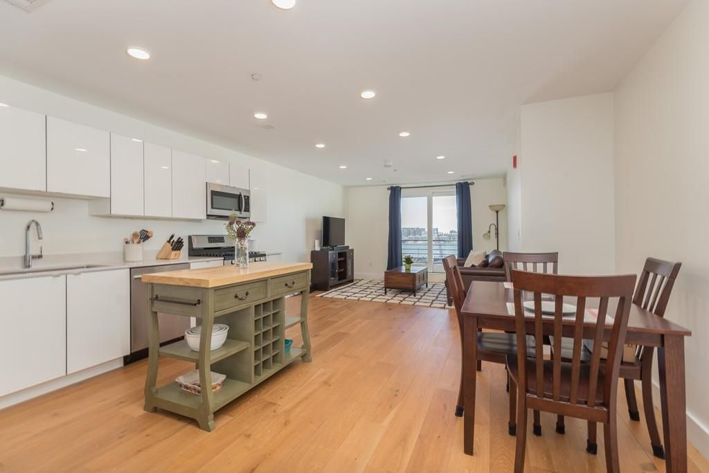 An open dining room-kitchen area leading to a living room with windows overlooking a harbor.