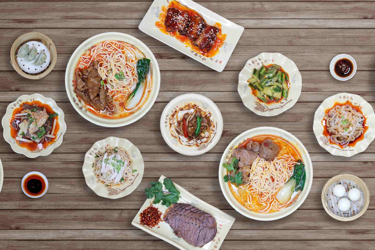 A spread of dishes from Sichuan Popo seen from above, including cold chicken, noodles, greens, and noodle soup
