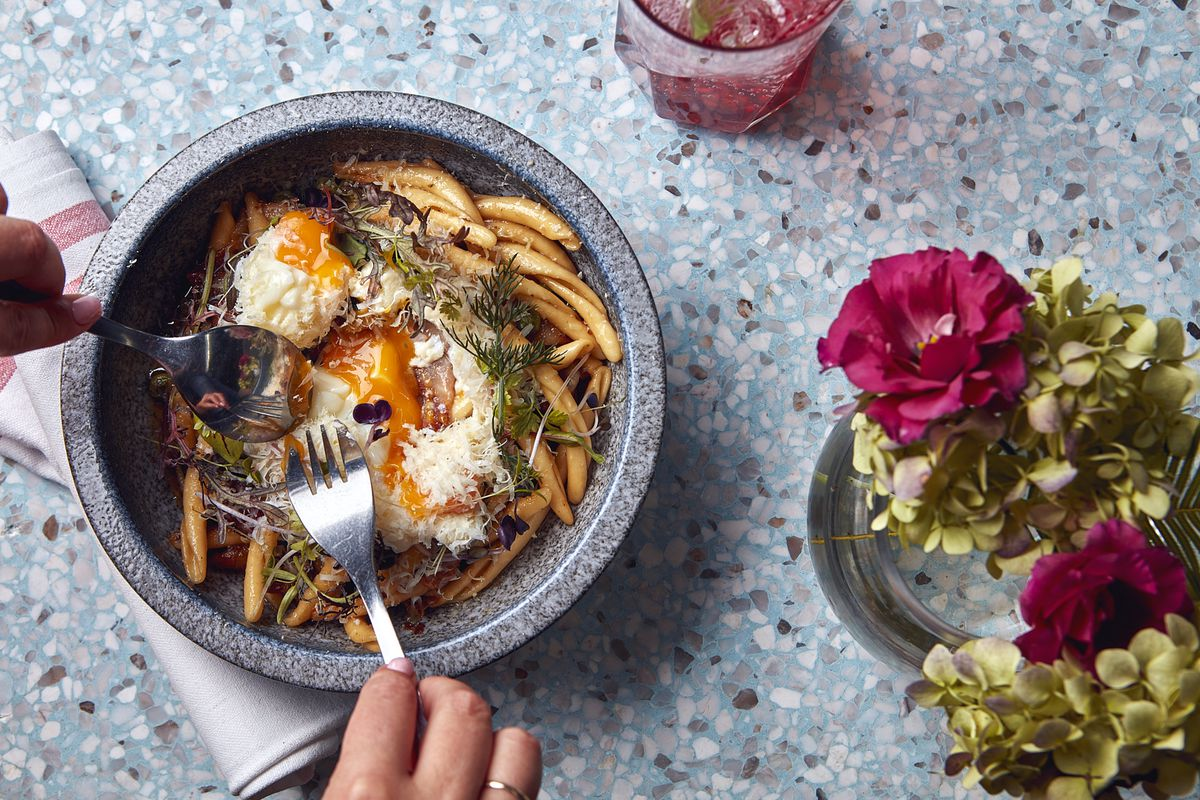 An overhead shot of a bowl with pasta, cheese, an egg and forks digging in on a terrazzo table with a vase of flowers