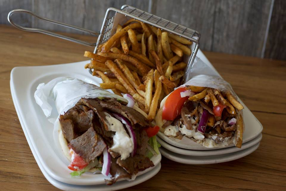 Two gyros with fries in the background