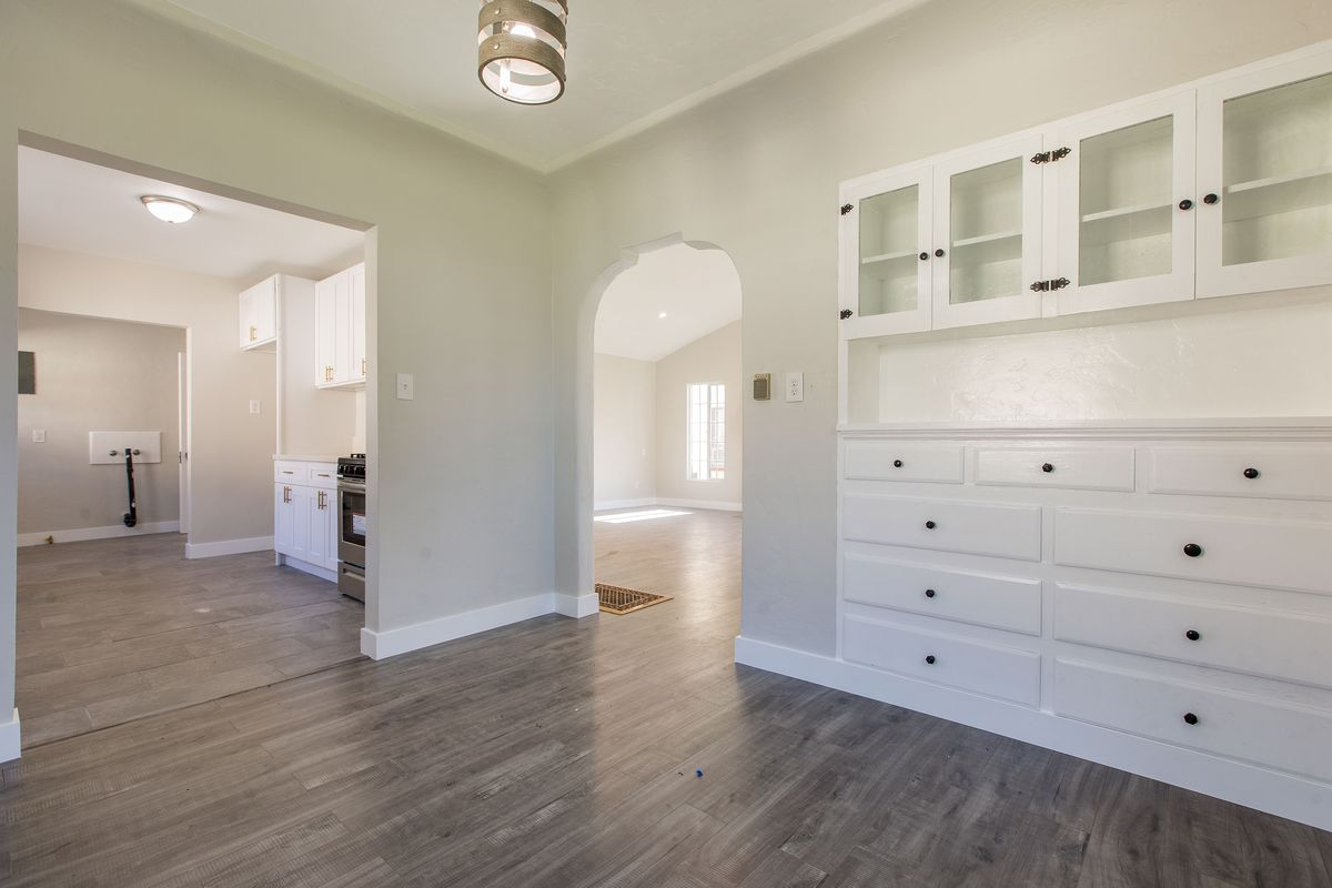 A built-in white cabinet is in the foreground. An arched doorways allows a view into the living room.