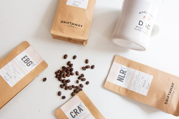 Four packages of coffee beans and a mug laid out on a white table