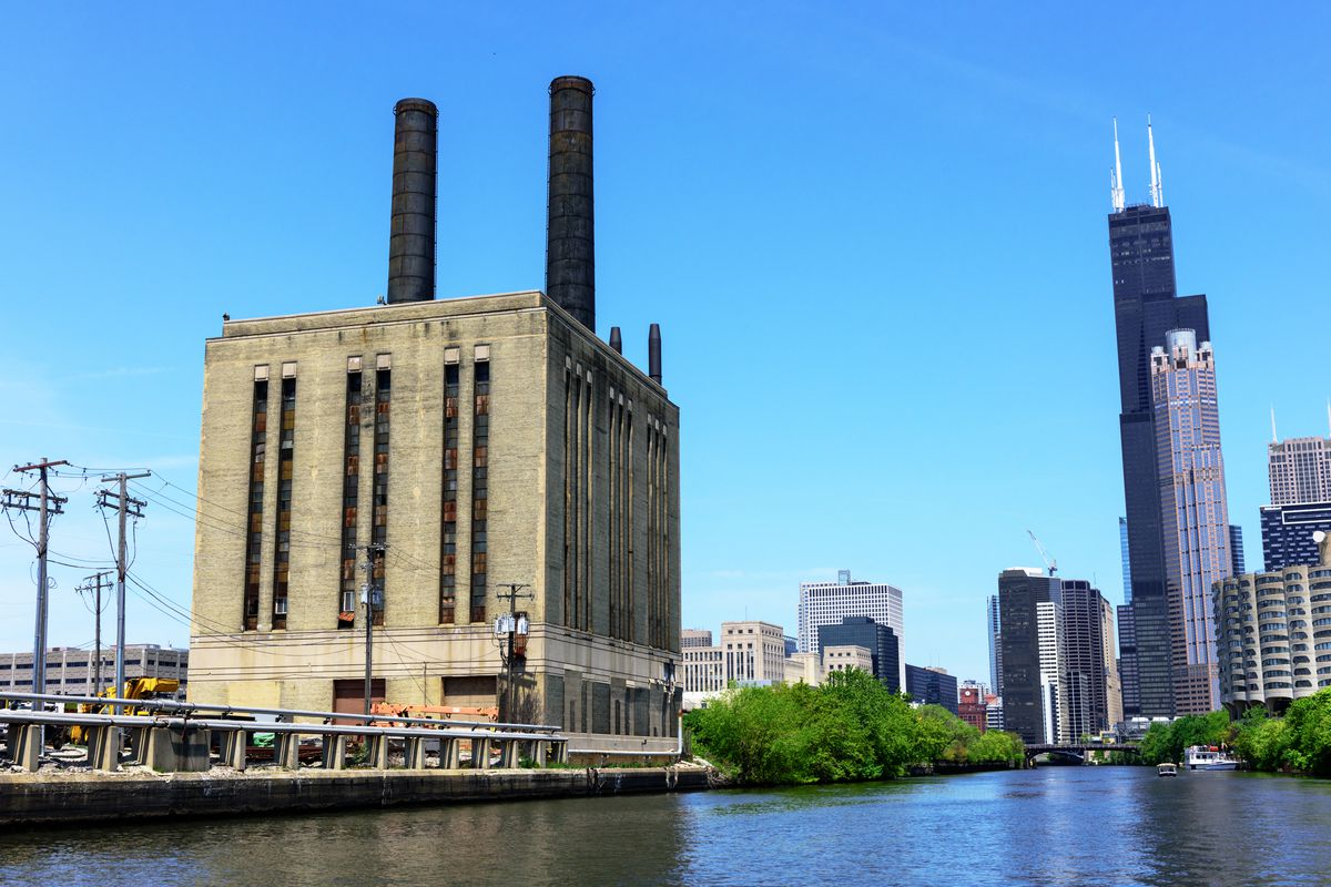 A beige brick power plant with twin smoke stacks stands next to a river. Taller skyscrapers stand in the distance.