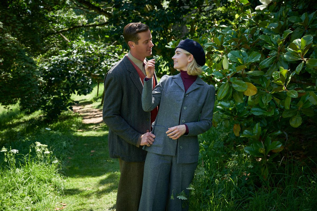 A man and a woman are standing on a leafy, tree-lined path. The main is wearing a suit and leaning toward the woman. The woman is wearing a pantsuit and beret and reaching up to touch the man's chin.