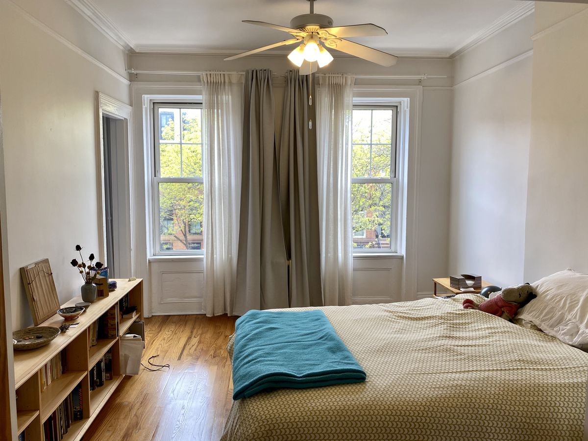 A bedroom with two large windows, beige walls, a ceiling fan, and a medium-sized bed.