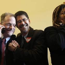 John Lewis, left, and his partner Stuart Gaffney embrace as they react next to Andrea Shorter after the Supreme Court decision at the office of San Francisco Mayor Ed Lee at City Hall in San Francisco, Wednesday, June 26, 2013.