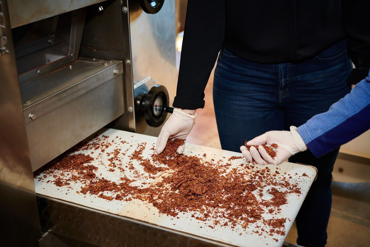 Two gloved hands hold chocolate shavings.
