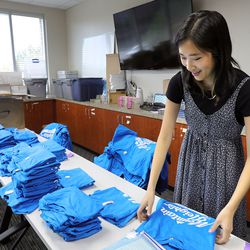Hannah Segura, Mountain Heights Academy student services, folds shirts for students during in-person orientation at the online school based in West Jordan on Tuesday, Aug. 24, 2021.