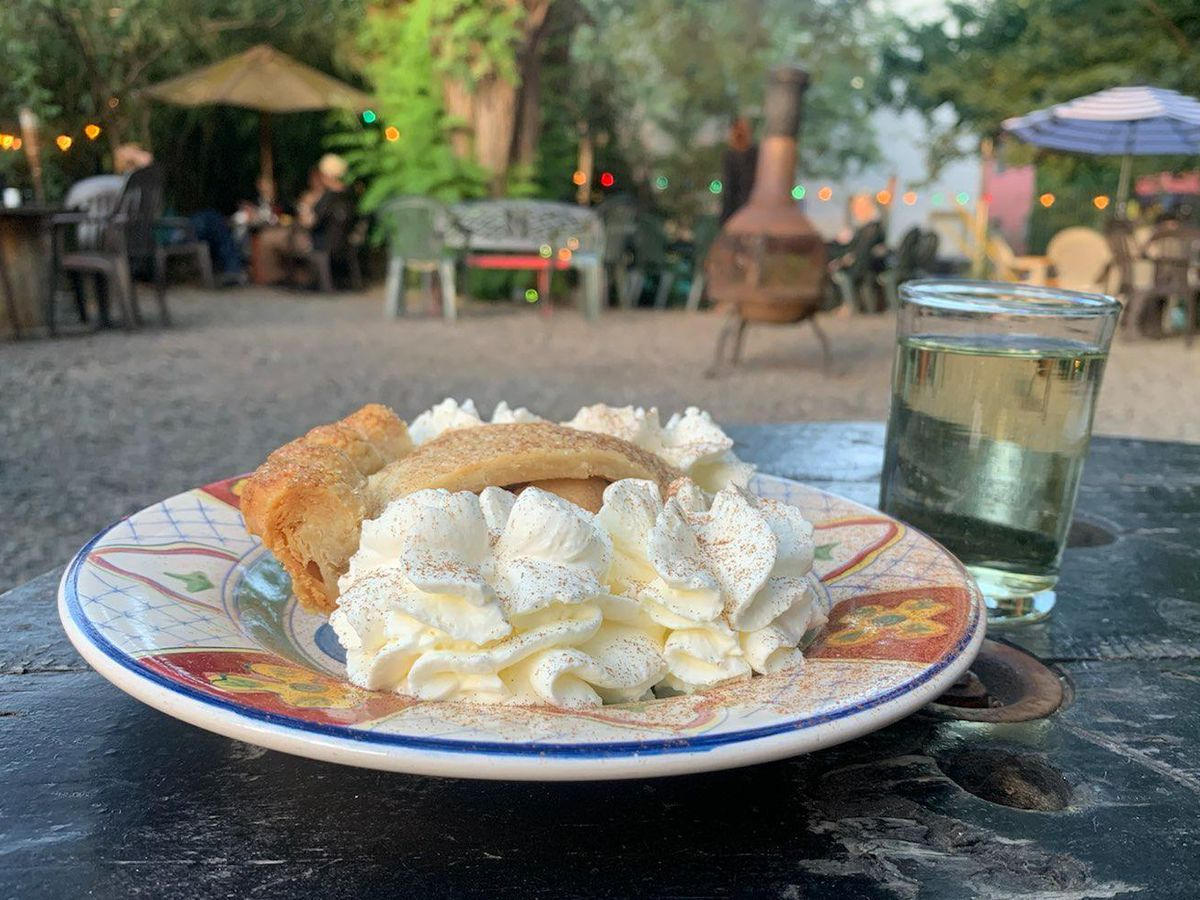 A painted plate sits on a worn black wooden table. The plate has a slice of pie surrounded by whip cream; next to it is small juice glass with prosecco.