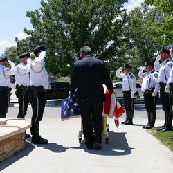 Policemen salute as the coffin of Judge Michael Kwan is moved toward the Taylorsville City Hall in Taylorsville on Friday, July 31, 2020.Kwan died July 21.
