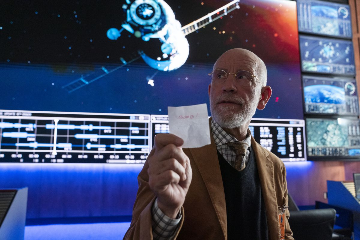 """Dr. Mallory (John Malkovitch) holds a paper that says """"Bomb!"""""""