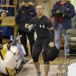 Nick Cunningham watches the clock after racing in the United States four-man bobsled team trials on Saturday, Oct. 26, 2013, in Park City, Utah. Cunningham and his crew came in second place. (AP Photo/Rick Bowmer)