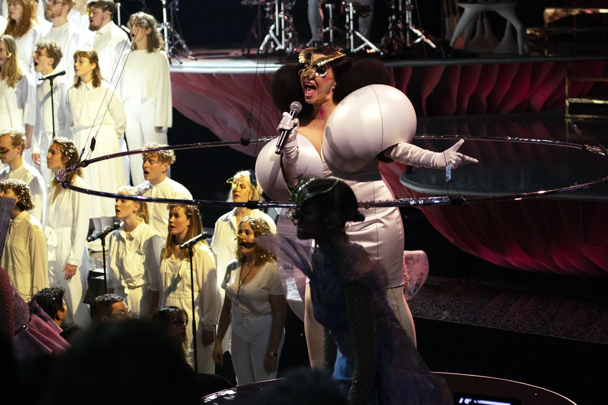 The artist Bjork performs on stage. She is wearing a white dress with two bulbous structures on top. There is a group of people in white clothing singing on stage with her.