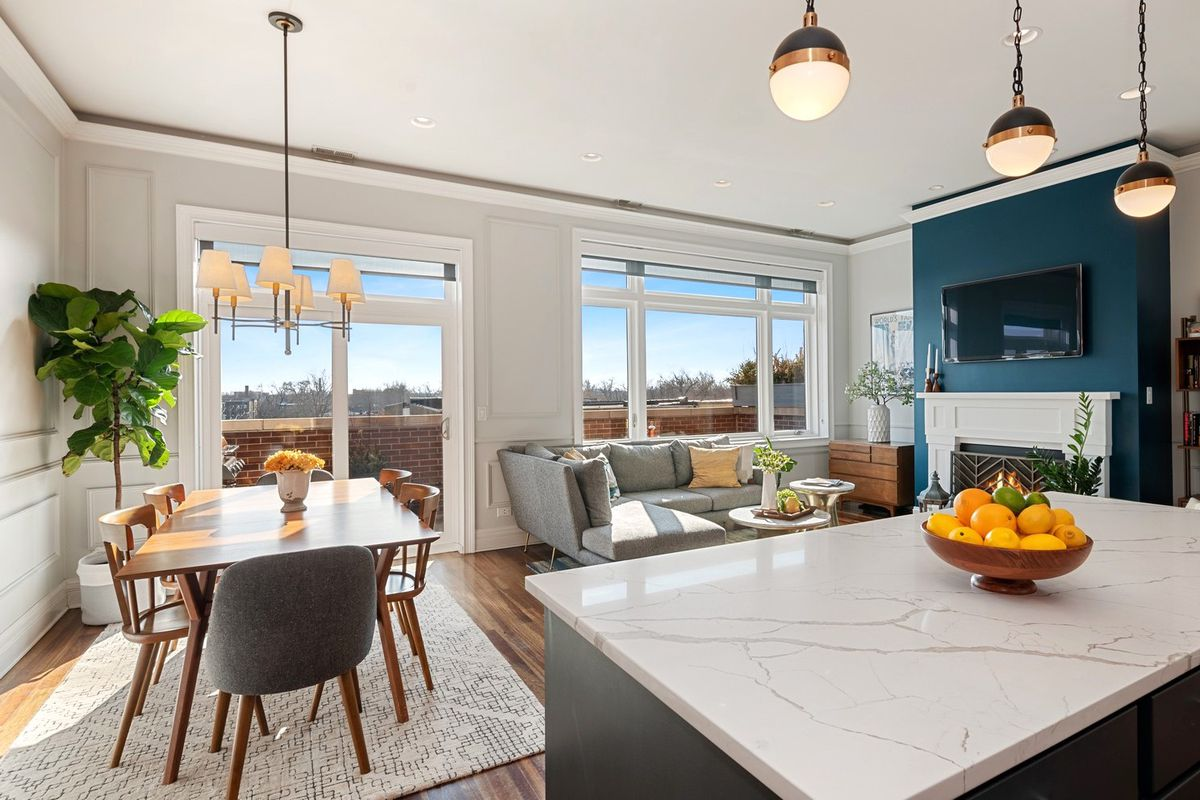 A condo with a large stone kitchen island, wood dining table, a gray sectional next to a fireplace.