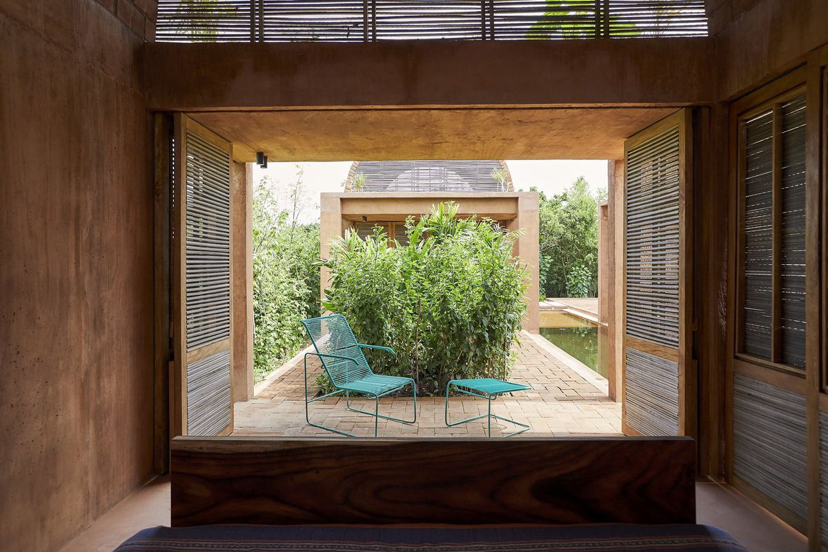 Reed lattice doors open onto a brick patio from a bedroom. A green chair and foot stool sit on the patio, and trees and a moat are behind the chair.