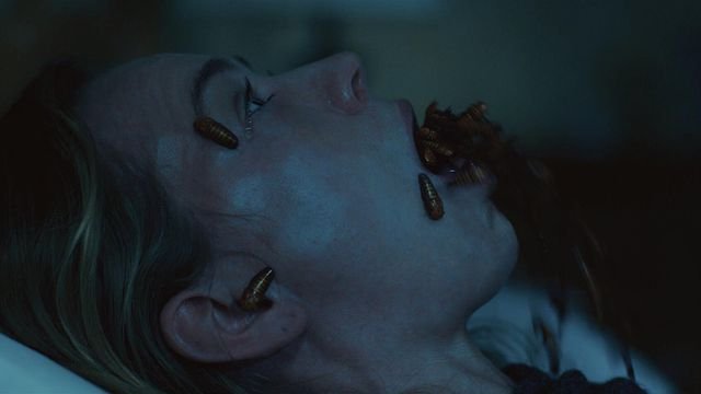 A woman on her back with insects crawling out of her mouth