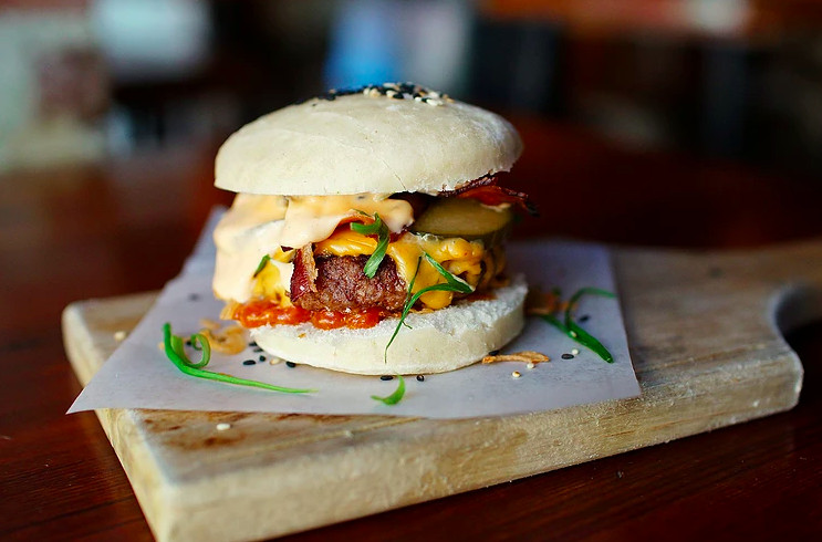A burger served on a steamed bun and topped with a kimchi cheese and bacon