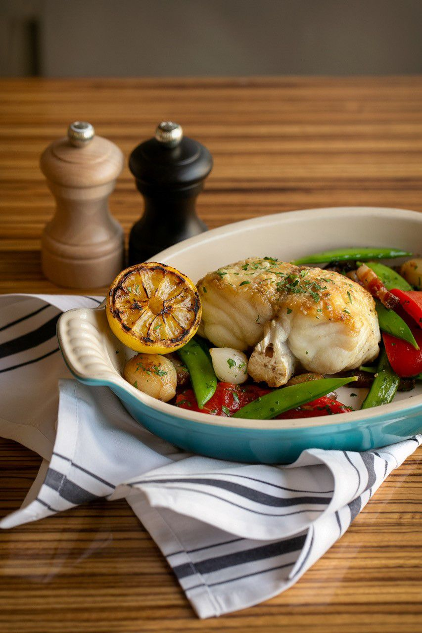 A Le Creuset serving dish holds bone-in monkfish en cocotte with roasted peppers, pearl onions, snap peas, and smoked bacon