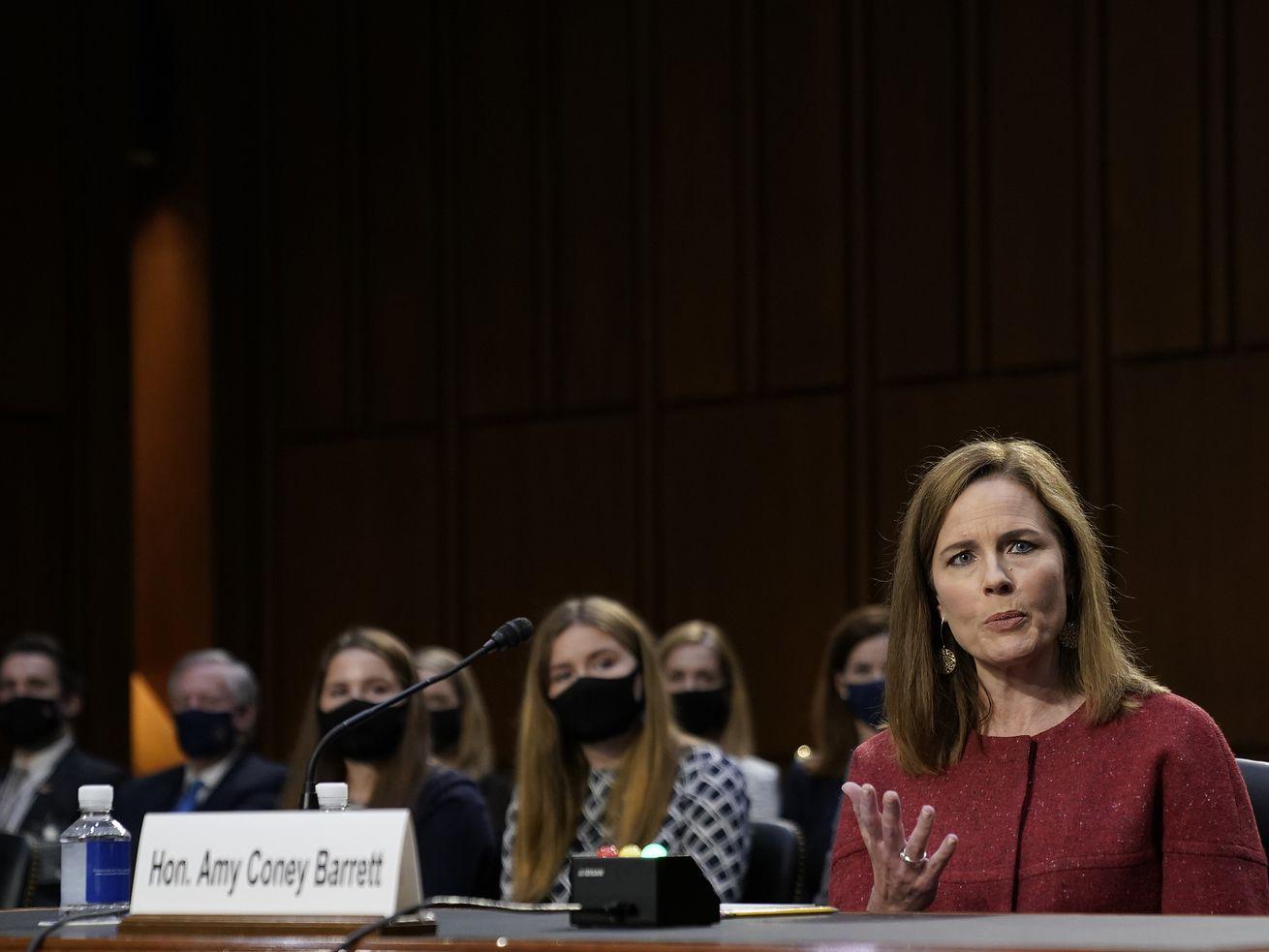 Amy Coney Barrett s'exprime dans une salle d'audience avec certains de ses enfants assis derrière elle.