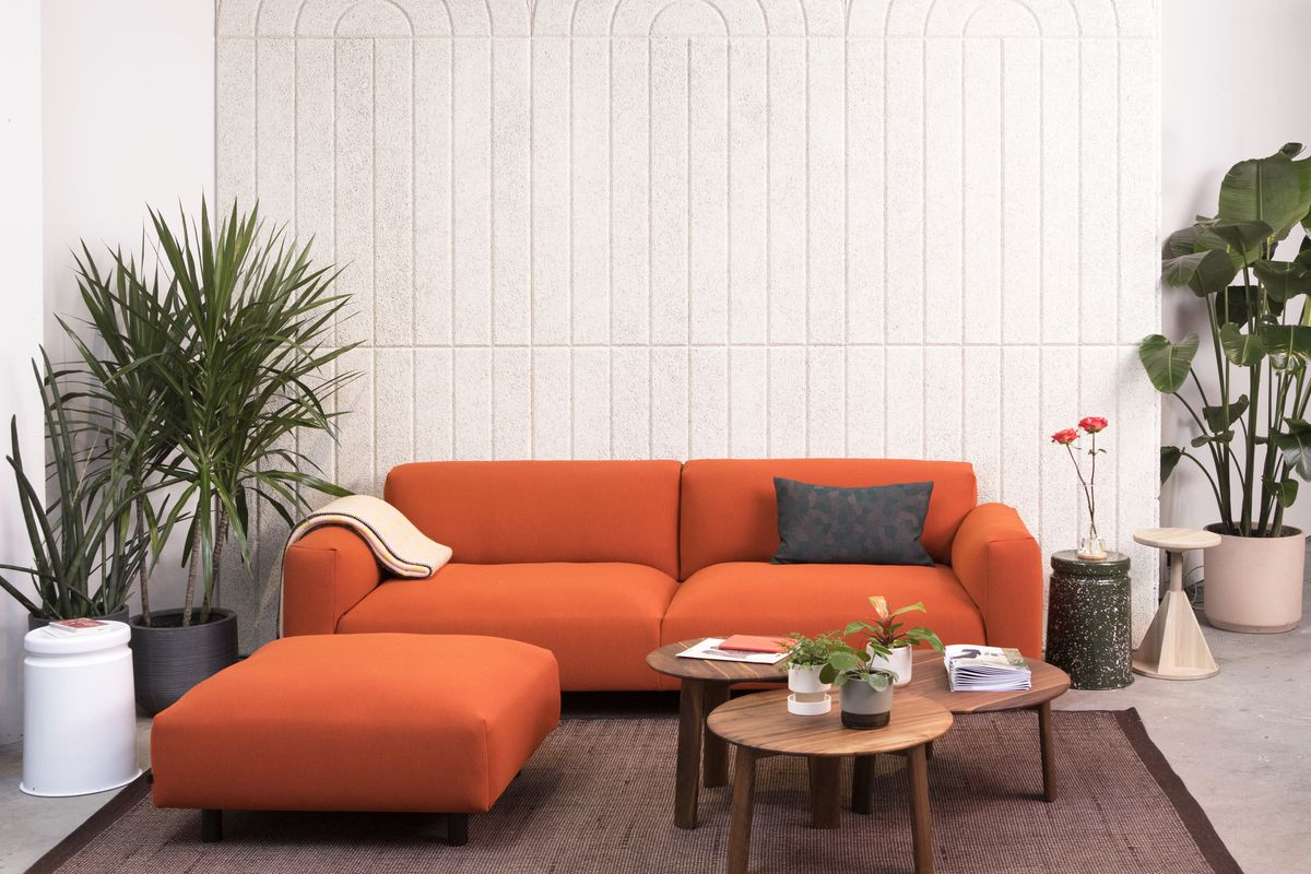 Scene of orange sectional couch on wool rug, with stools, coffee tables, and plants surrounding it.