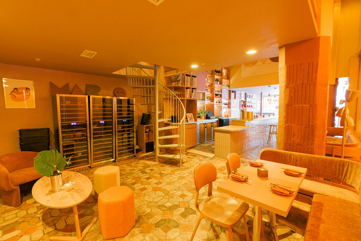 dining room in pastel colors, wooden chairs, tile flooring, staircase, bar in the background
