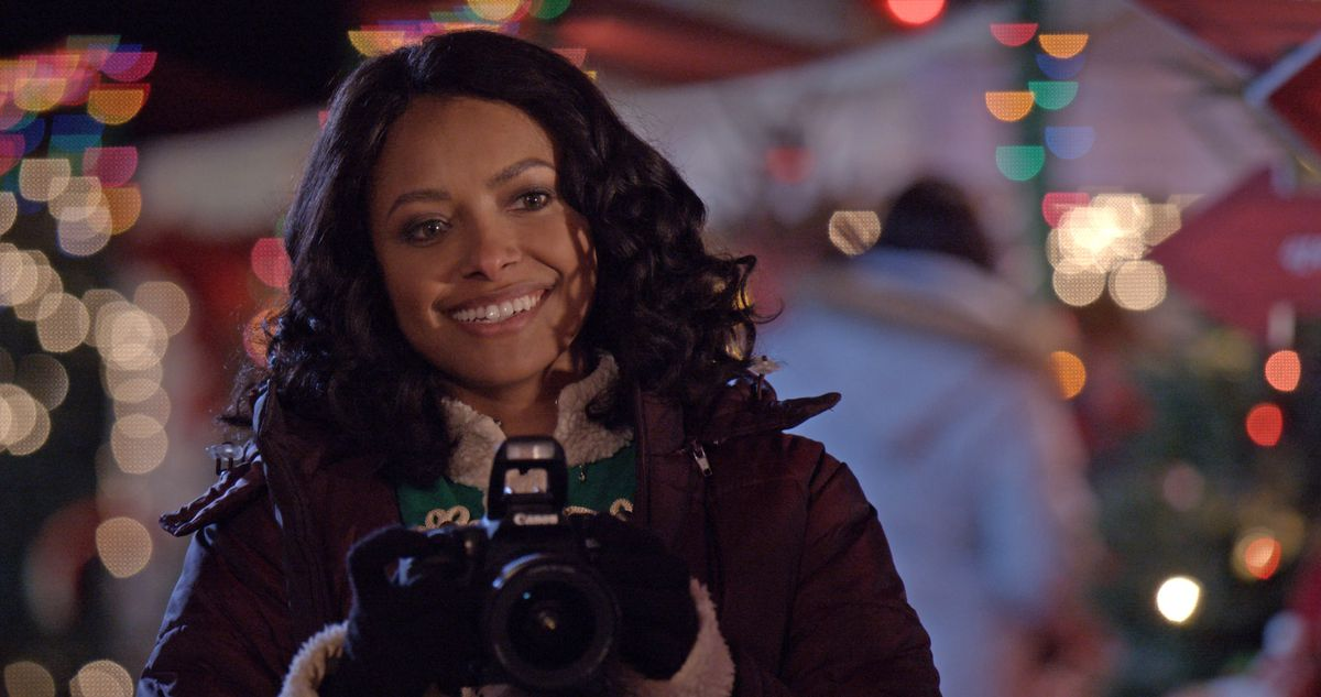 Abby (Kat Graham) holds up a camera.