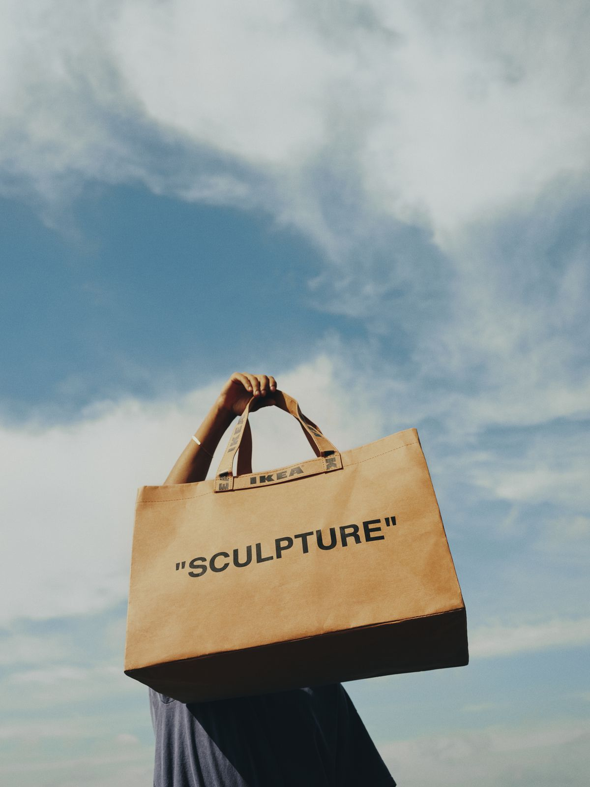 """Person holding brown paper shopping bag that says """"Sculpture."""""""