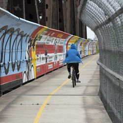 A local cyclist bikes along the 400-ft Major Taylor Trail Mural, located on a pedestrian bridge on Little Calumet River, painted by Chicago artist and muralist Bernard Williams.