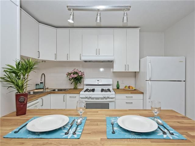 Condo kitchen with white cabinets, butcher block countertops and two place settings at bar