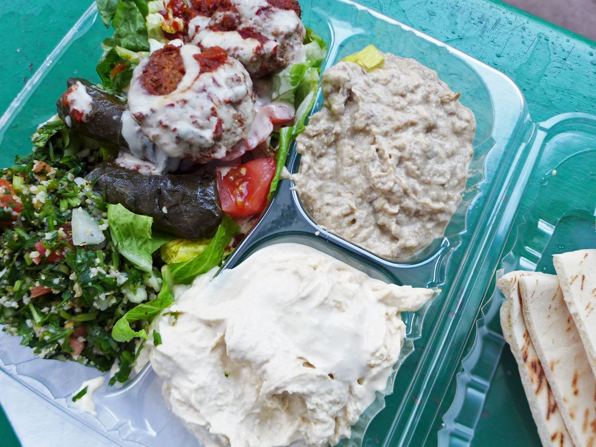 Vegetarian platter with six dishes in a plastic container.