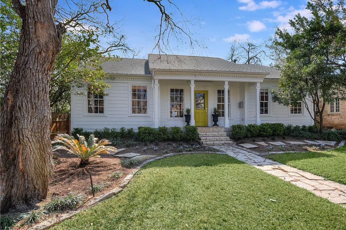 one story symmetrical 1937 clapboard house white with yellow door, yard in front
