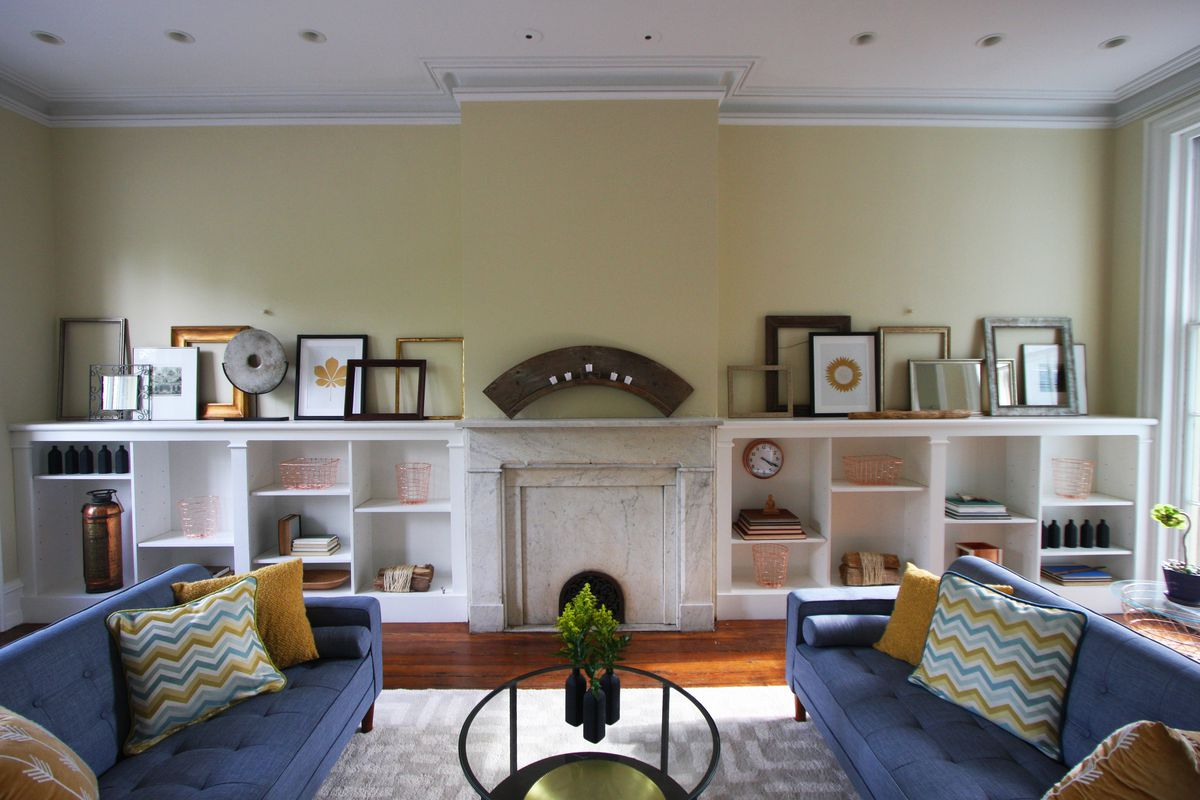 A large living room with a marble mantle fireplace sandwiched by built-in bookcases.