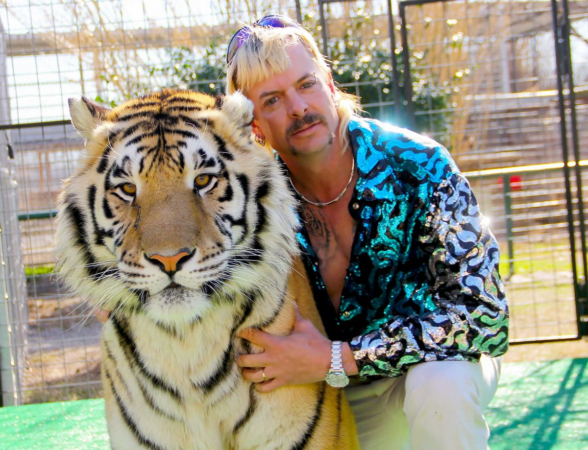 A dyed-blonde, mulleted man in a reflective blue-and-silver jacket hugs a tiger, with his head up against its head.