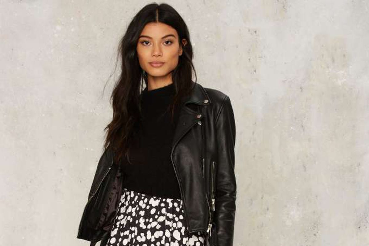 0ed2bc3de8d4 Model in black moto jacket, black sweater, and patterned skirt. Photo: Nasty  Gal Racked ...