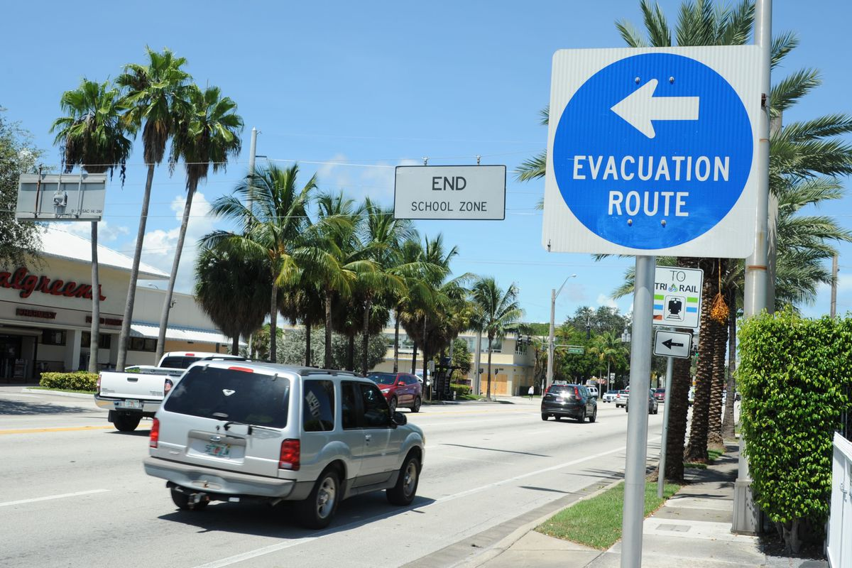 A sign in Fort Lauderdale, Florida directs travelers to the evacuation route down a palm-lined street in expectation of Hurricane Irma.