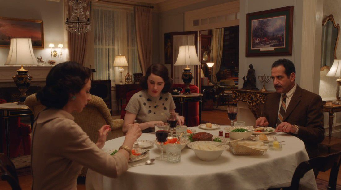 Two women and one man eating at a dinner table.